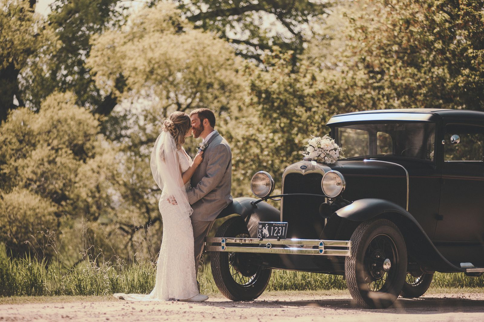 Newcastle WY wedding couple posed on a vintage car